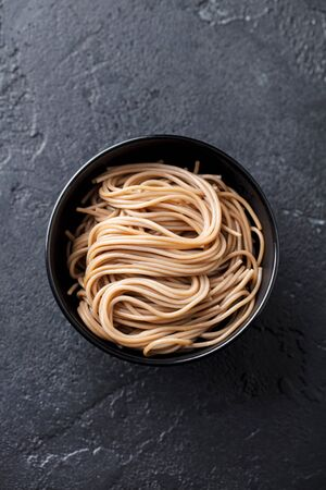 Soba noodles on a black bowl. Japanese food. Slate background. Top view.