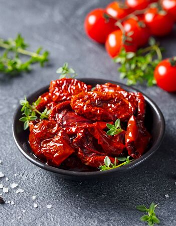 Sun dried tomatoes with fresh herbs and spices. Slate background. Close up.