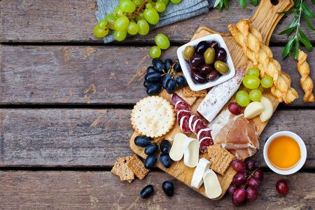 Cheese and meat appetizers on cutting board on wooden background. Copy space. Top view. Banco de Imagens