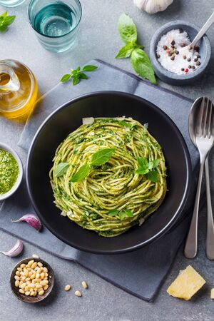 Pasta spaghetti with pesto sauce and fresh basil leaves in black bowl. Grey background. Top view. Banco de Imagens