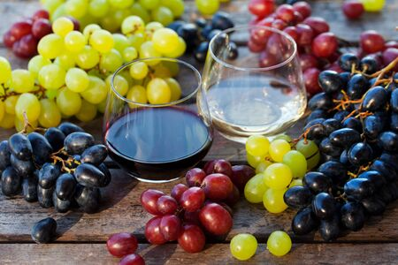 Glass of red and white wine with fresh grape assortment on wooden table. Close up. Banco de Imagens