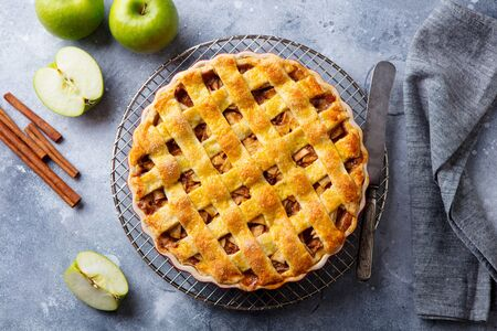 Apple pie with caramel on a cooling rack. Grey background. Top view.