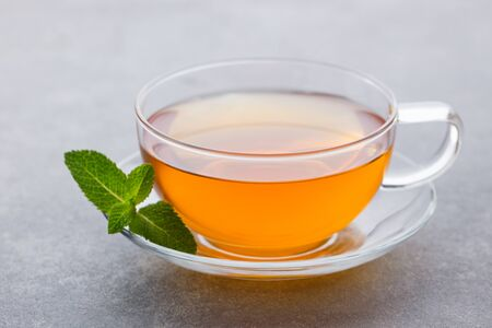 Tea cup with mint leaf. Grey background. Close up.