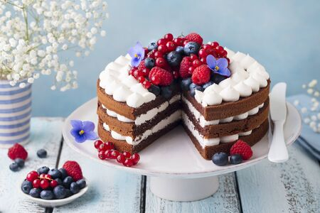 Chocolate cake with whipped cream and fresh berries. Blue wooden background. Close up.