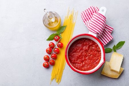 Traditional tomato sauce in saucepan with spaghetti pasta. Grey background. Copy space. Top view. Banco de Imagens