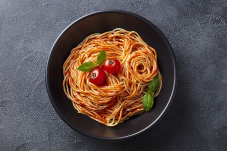 Pasta, spaghetti with tomato sauce in black bowl. Slate background. Top view.