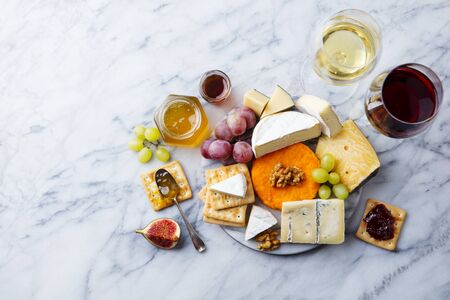 Assortment of cheese, grapes with red and white wine in glasses. Marble background. Top view. Copy space.