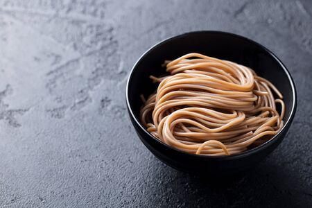 Soba noodles on a black bowl. Slate background. Copy space. Banco de Imagens