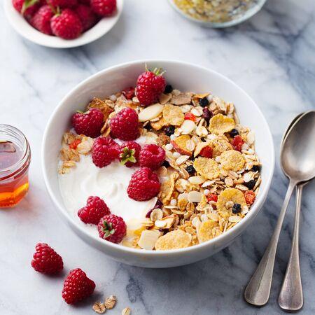 Healthy breakfast. Fresh granola, muesli with yogurt and berries. Marble background. Close up.