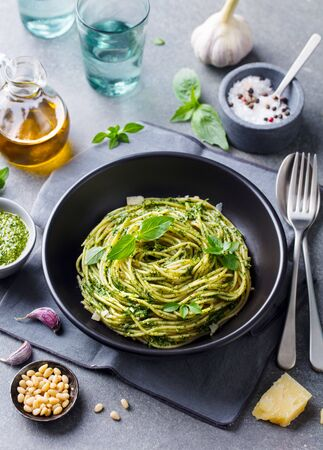 Pasta spaghetti with pesto sauce and fresh basil leaves in black bowl. Grey background. Banco de Imagens