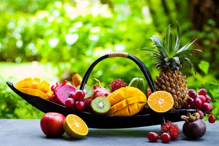 Tropical fruits assortment in wooden boat. Outdoor tropical background. Copy space.