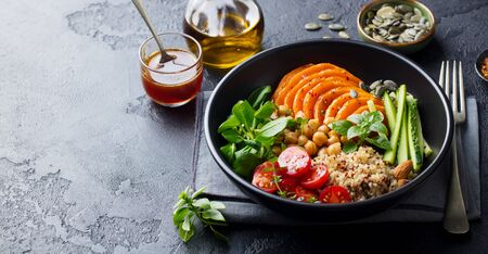 Healthy vegetarian salad. Pumpkin, quinoa, chickpea, tomatoes, green salad. Buddha bowl. Slate background. Copy space.