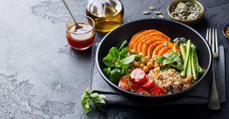 Insalata vegetariana sana. Zucca, quinoa, ceci, pomodori, insalata verde. Ciotola del Buddha. Sfondo di ardesia. Copia spazio.