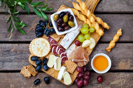 Cheese and meat appetizers on cutting board on wooden background. Top view. Banco de Imagens