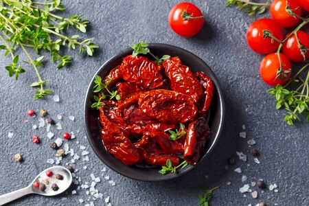 Sun dried tomatoes with fresh herbs and spices. Slate background. Top view.