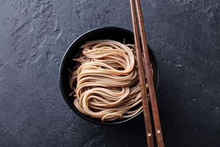 Soba noodles on a black bowl with wooden chopsticks. Slate background. Top view. Banco de Imagens