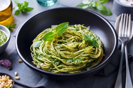 Pasta spaghetti with pesto sauce and fresh basil leaves in black bowl. Grey background. Close up.