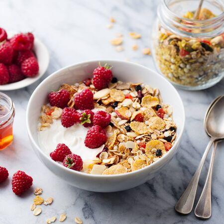 Healthy breakfast. Fresh granola, muesli with yogurt and berries. Marble background. Close up Stock fotó
