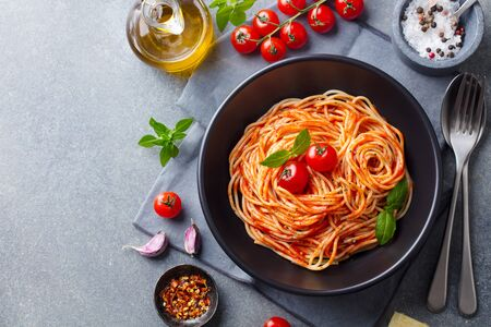 Pasta, spaghetti with tomato sauce in black bowl on grey background. Copy space. Top view.