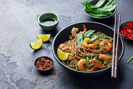 Stir fry noodles with vegetables and shrimps in black bowl. Slate background. Close up. Copy space.