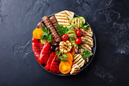 Grilled meat kebabs and vegetables on a black plate. Black stone background. Top view.