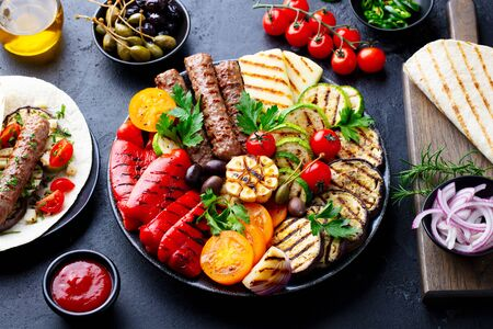 Grilled meat kebabs, vegetables on a black plate with tortillas, flat bread. Slate stone background.