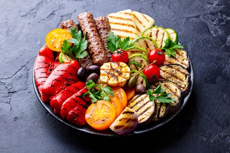 Grilled meat kebabs and vegetables on a plate. Black stone background. Close up.