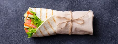 Wrap sandwich, roll with fish salmon and vegetables. Dark background. Top view.