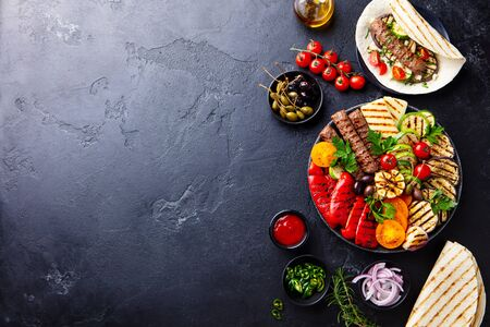 Meat kebab, vegetables on a black plate with tortillas, flat bread. Slate stone background. Copy space. Top view.