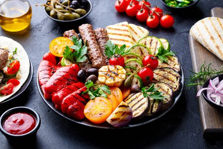 Grilled meat kebabs, vegetables on a black plate with tortillas, flat bread. Slate stone background. Close up.