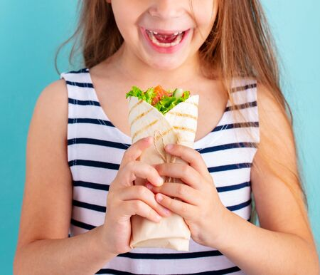 Happy beautiful child girl eating wrap sandwich. Blue background. Close up.