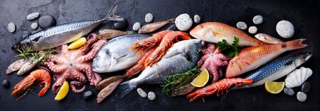 Fresh fish and seafood assortment on black slate background. Top view. Stock Photo