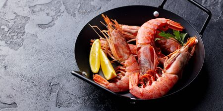 Prawns with lemon and fresh herbs in a black frying pan. Stone background. Copy space