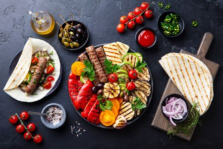 Grilled meat kebabs, vegetables on a black plate with tortillas, flat bread. Slate stone background. Top view