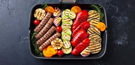 Grilled meat kebab and assortment vegetables in grill pan. Black stone background. Top view.