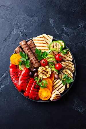 Grilled meat kebabs and vegetables on a black plate. Black stone background. Top view. Stok Fotoğraf - 140528089