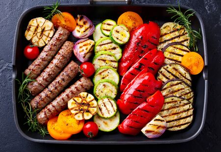 Grilled meat kebab and vegetables in grill pan. Black stone background. Top view.