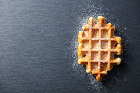 Belgian waffle with icing sugar. Slate background. Copy space. Top view.