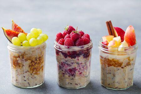 Assortment overnight oats, bircher muesli with fresh berries and fruits in a glass jars. Grey background. Reklamní fotografie