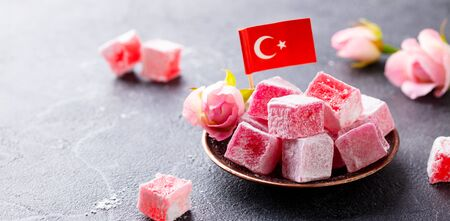 Turkish delight, rose flavour in a copper plate with Turkish flag. Grey stone background. Copy space.