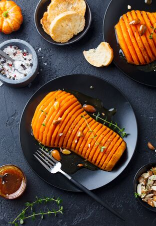 Roasted pumpkin with honey glaze and herbs on a black plate. Dark background. Top view.