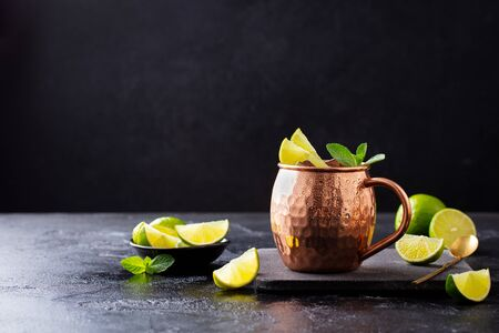 Cold Moscow Mules cocktail with ginger beer, vodka, lime and mint. Grey stone background. Copy space. Stock Photo