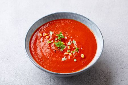 Tomato soup with fresh herbs and pine nuts in a bowl. Grey stone background. Close up. Archivio Fotografico