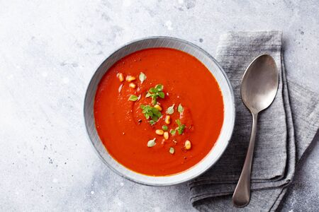 Tomato soup with fresh herbs and pine nuts in a bowl. Grey stone background. Top view. Foto de archivo