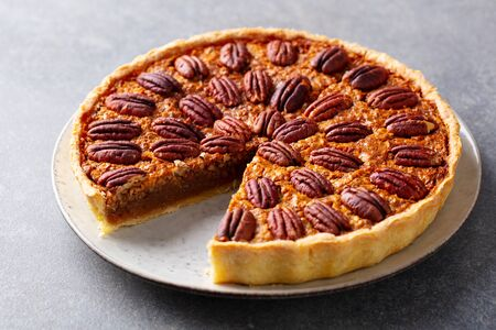 Pecan nut pie, tart on a plate. Grey background. Close up.