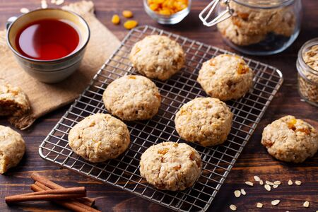 Oat vegan cookies on cooling rack with cup of tea. Wooden background.