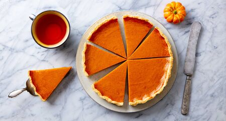 Pumpkin pie on plate with cup of tea. Marble background. Top view.
