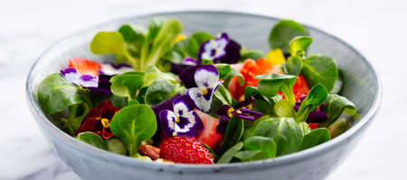 Fresh green salad with strawberries and edible flowers in a bowl. Marble background. Close up. Stock Photo