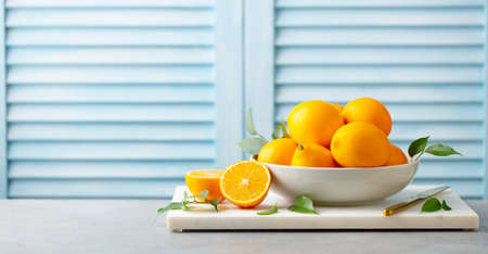 Fresh Meyer lemons in white bowl on marble board. Blue background. Copy space.