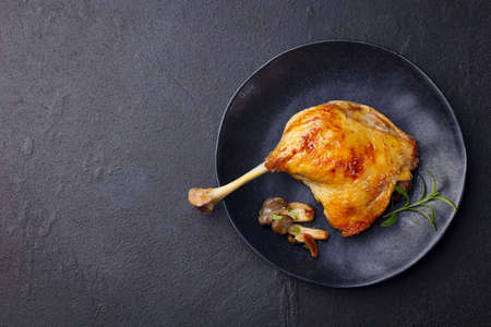 Duck leg confit with mushroom sauce on black plate. Slate background. Copy space. Top view.